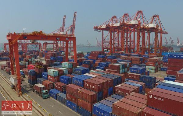 资料图片:这是工人在唐山港京唐港区集装箱货场操纵机器装备调运集装箱。(7月16日摄)