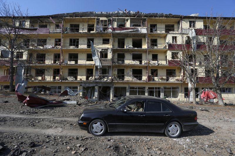 资料图:一名男子驾车驶过冲突区域。(图源:路透社)