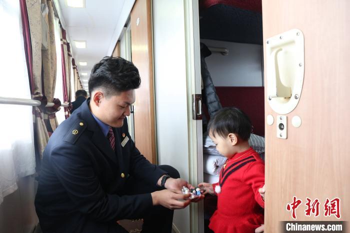 乘务人员捏制卡通吉祥物,送给乘车小旅客。 方正 摄
