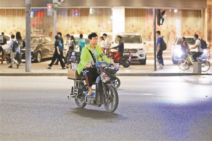 南山大道上,一名没有戴头盔的快递员,骑着电动自行车在机动车道上横冲直撞。 深圳晚报记者 张焱焱 摄