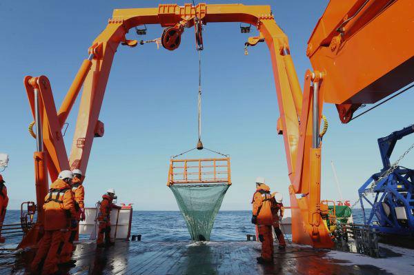"""2020年1月5日,科考队员在""""雪龙2""""号船尾布放大型底栖生物拖网。(新华社)"""