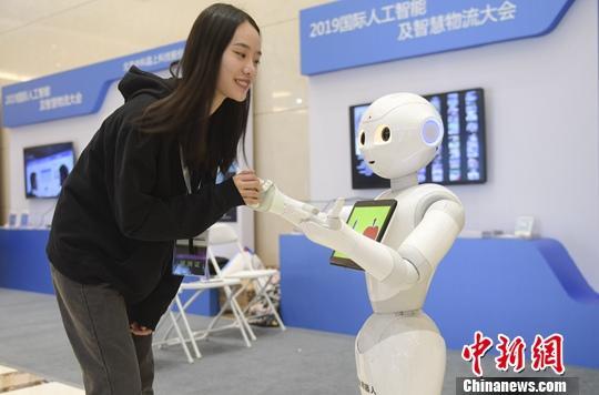 资料图:嘉宾与机器人交流。中新社记者 张勇 摄