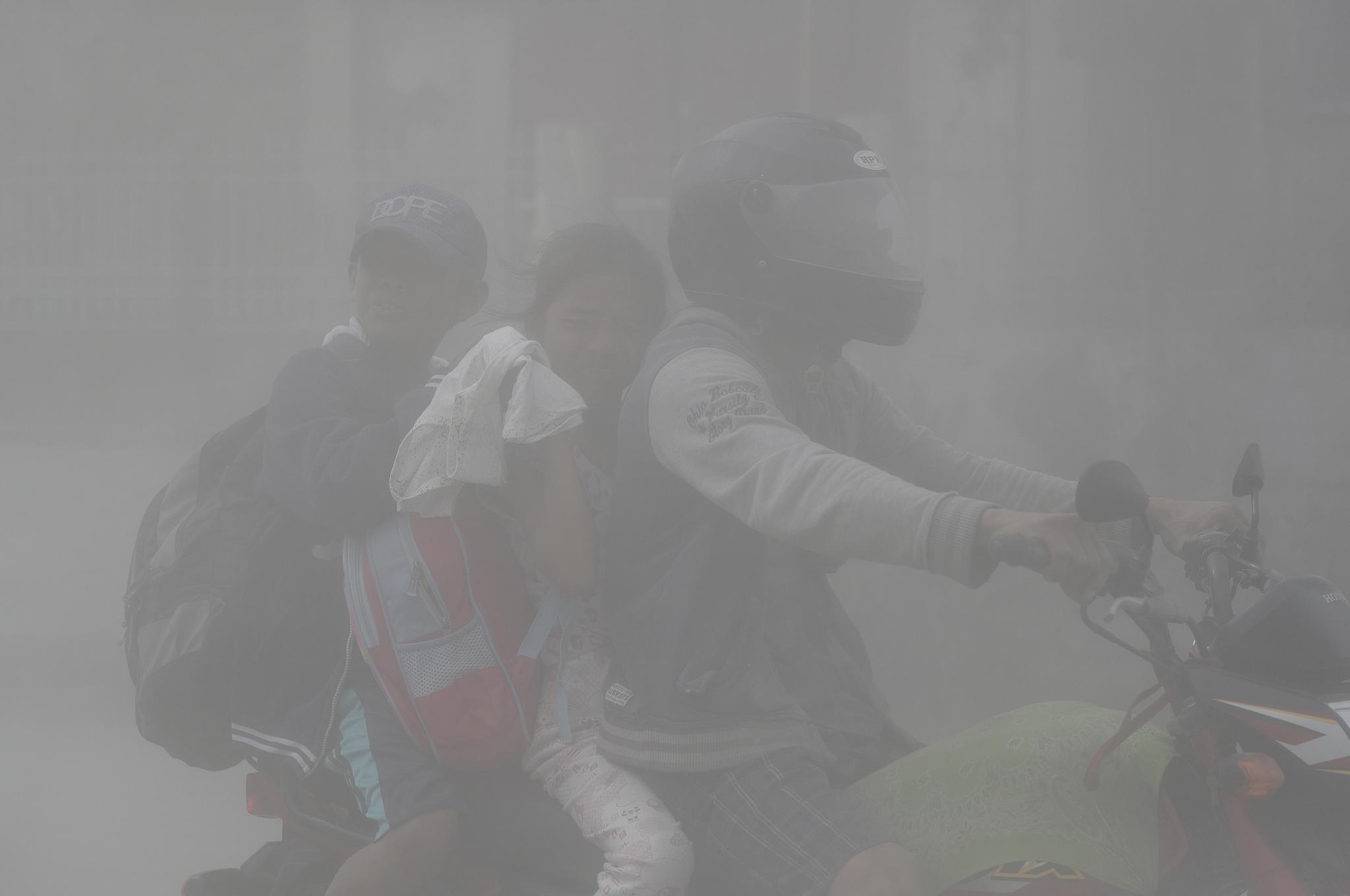 ▲1月13日,在菲律宾甲米地省塔盖泰,人们在火山灰的笼罩下出行。|新华社