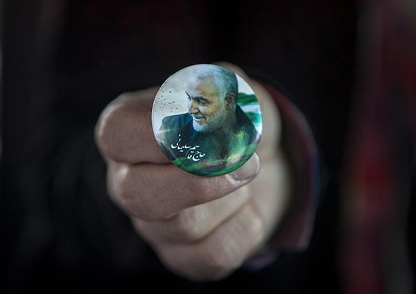 """1月5日,在伊朗首都德黑兰,一名男子展示悼念伊朗伊斯兰革命卫队下属""""圣城旅""""指挥官苏莱曼尼的徽章。新华社 资料图"""