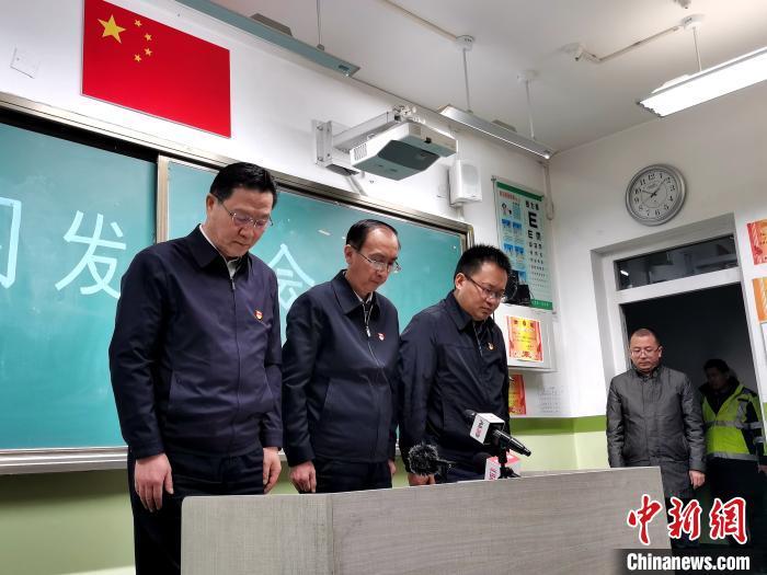 图为西宁市官方14日22时许召开的新闻发布会,为遇难者默哀。 张添福 摄