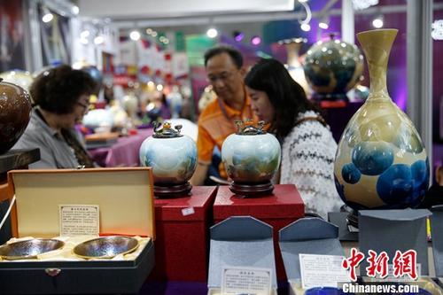 资料图:在哈尔滨举行的第六届中国-俄罗斯博览会上,参观者挑选台湾陶瓷工艺品。中新社记者 吕品 摄