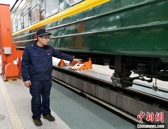 信松向记者介绍旅客列车制动阀。 杨杰英 摄