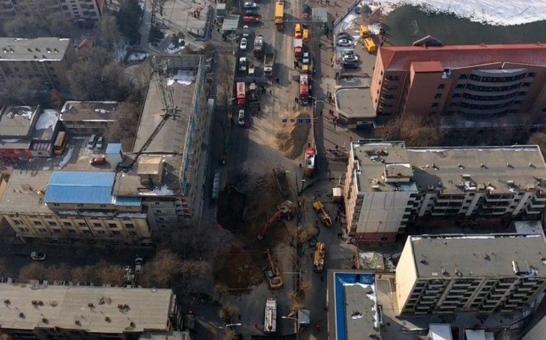 1月14日12时20分,挖掘机和渣土车扩大坑洞,搜救失踪人员,坑洞的直径已达十几米。 新京报记者 马骏 摄