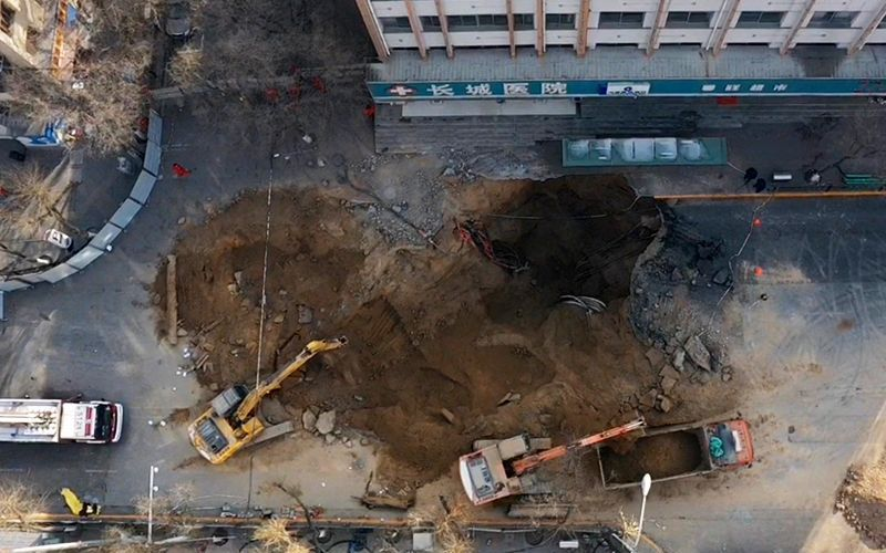 1月14日12时20分,救援人员使用挖掘机和渣土车扩大坑洞,挖出泥土和砂石,寻找失踪人员。新京报记者 马骏 摄