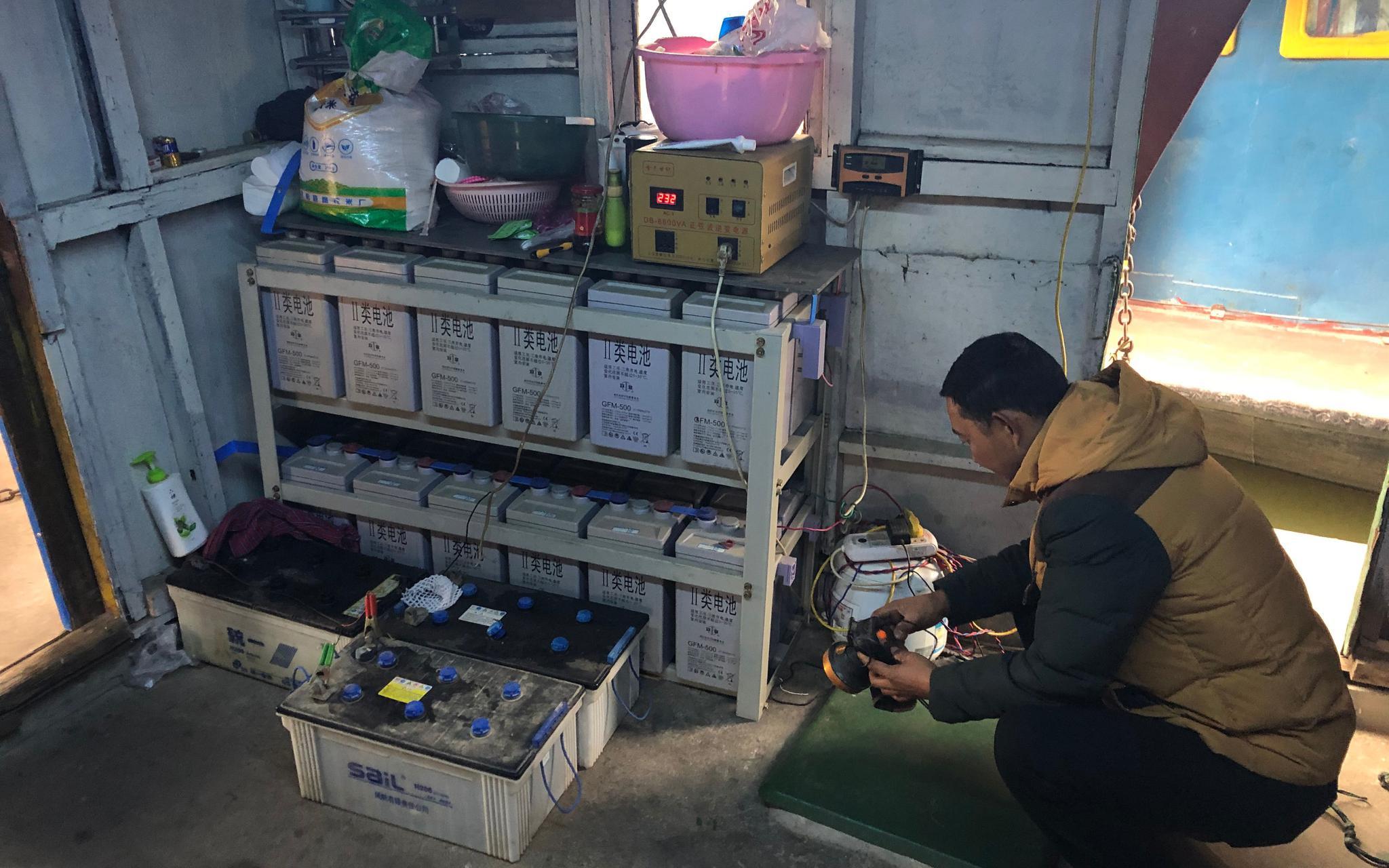 胡存库在船上给灯充电。为了用上稳定的电源,他在两年前购入了这些蓄电池。新京报记者 韩沁珂 摄