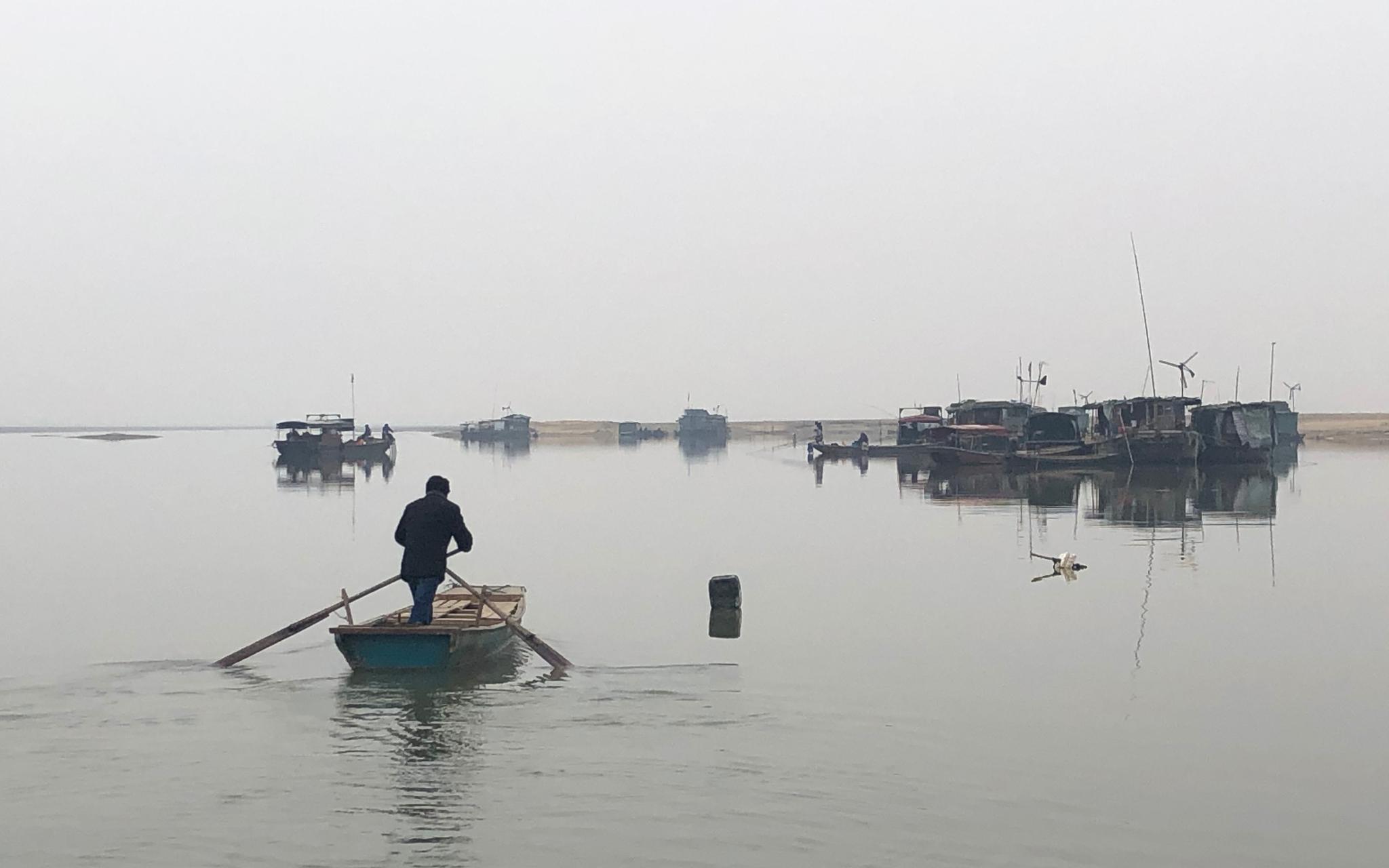 渔民划着小木船驶向停在湖中的生活船。新京报记者 韩沁珂 摄