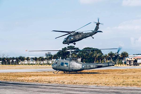 """由UH-1H直升机代表将象征执行吊挂任务的""""U形环"""",正式交接给黑鹰直升机代表。 图片来源 台媒"""