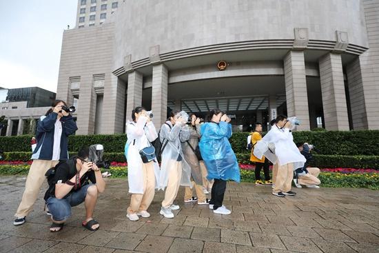 2019年10月2日,上海一所中学的摄影社成员在上海市政府门口冒雨拍摄升旗仪式。陈淑珉/摄