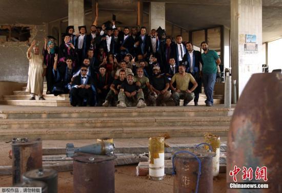 资料图:当地时间2016年10月24日,利比亚班加西,班加西大学化学工程专业的学生在战火毁坏的教学楼前拍毕业照。