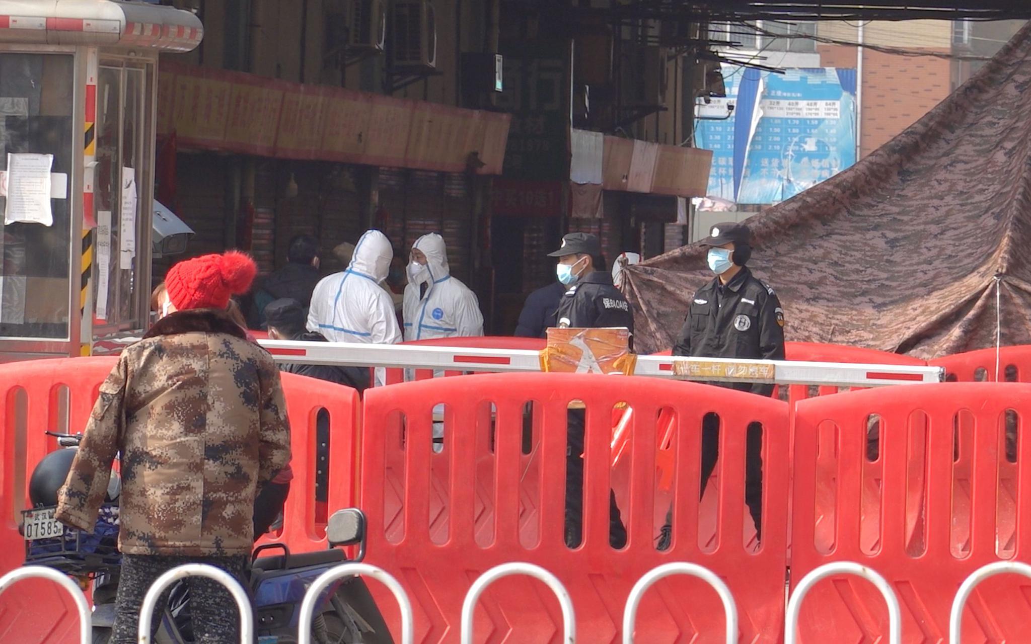 1月20日上午,武汉华南海鲜市场内,多身穿白色防护服的工作人员正在进行防疫工作。新京报记者游天燚摄