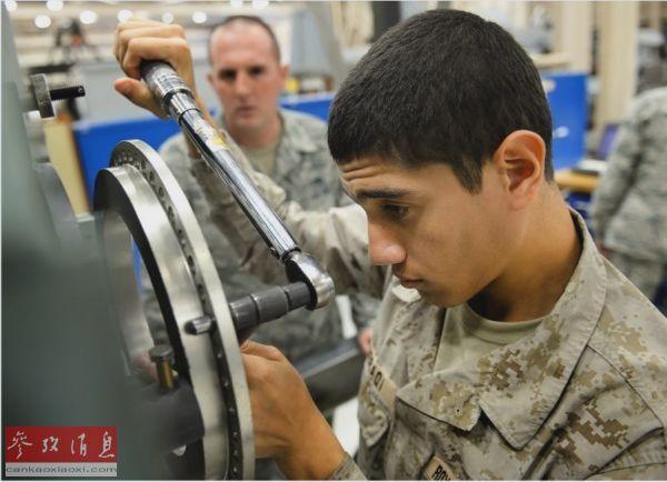 资料图片:一名沙特空军学员(右)在美学习维护战机发动机。(美国《星条旗报》网站)
