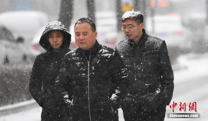 """资料图:兰州迎来降雪天气。当日是二十四节气中最后一个节气""""大寒""""。图为市民雪中出行。中新社记者 杨艳敏 摄"""