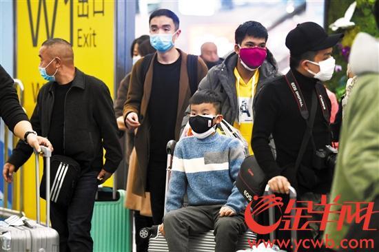 21日晚, 广州白云机场T1到达区,不少旅客面戴口罩 记者 梁喻 摄