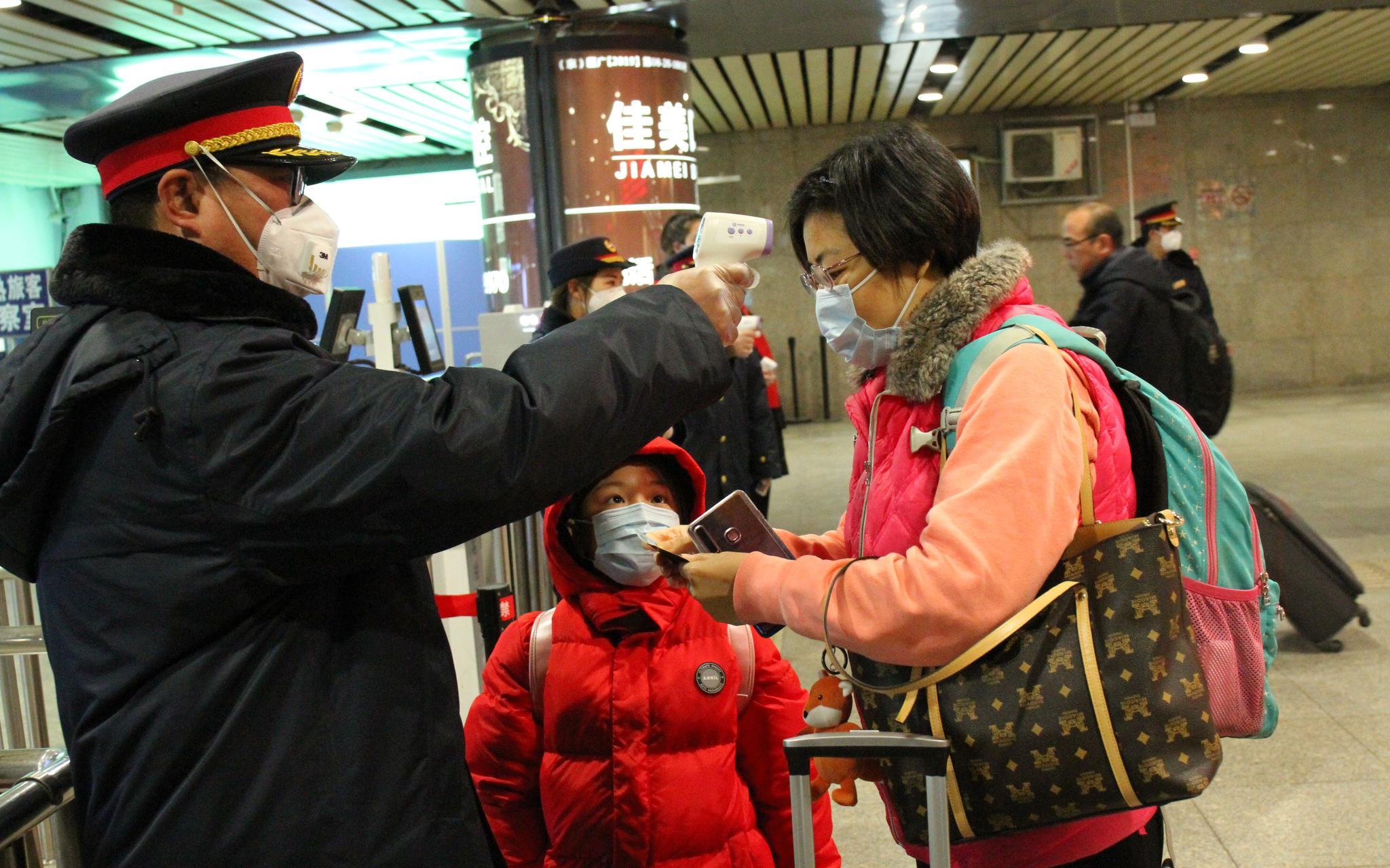 北京西站,工作人员正在用手持额温枪为旅客进行体温测试。北京西站供图