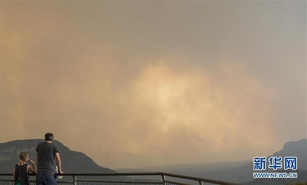 2019年12月21日,在澳大利亚新南威尔士州蓝山地区,市民远远观察山火。 新华社记者 白雪飞 摄