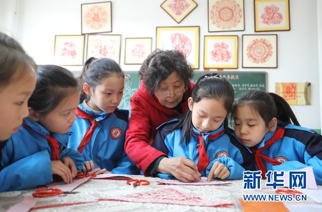 冯金兰在平定县东关小学教授剪纸。新华网 武斌 摄