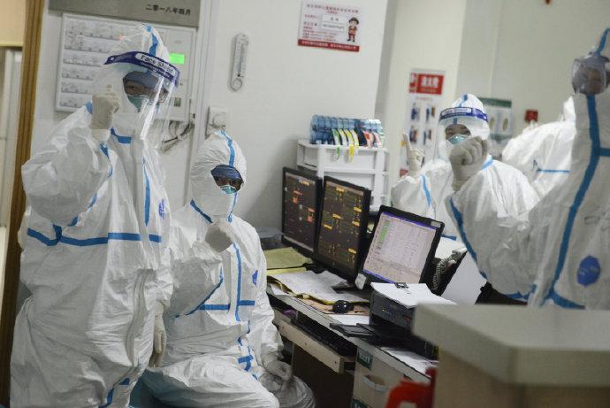 武汉中心医院诊治新型赢咖2肺炎现场:医护人员握拳相互鼓励图片