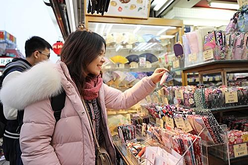 在日本东京浅草,游客在商店街上选购商品。(新华社)