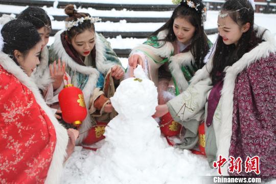资料图:古装美女堆雪人。 戴佳阳 摄