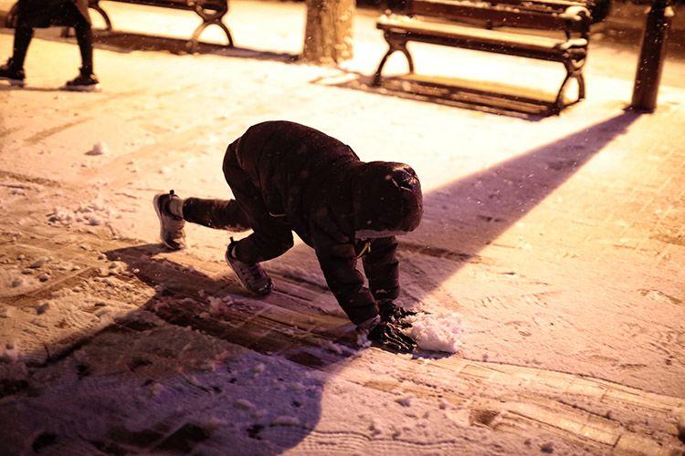 向阳北路,一位小伴侣正在兴奋地撮雪。