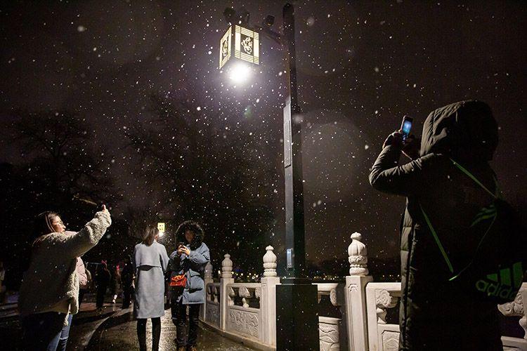 什刹海岸边,游客借着灯光拍照雪花飘落。