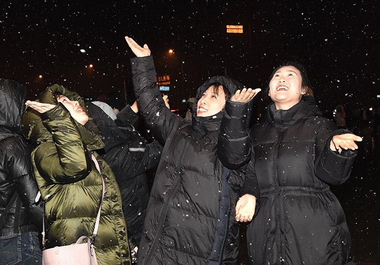 向阳区合生汇门前,市民用手接着雪花。
