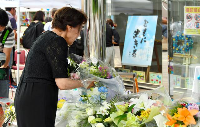 家属在相模原市残疾人福利院为逝去的亲人献花(朝日新闻)