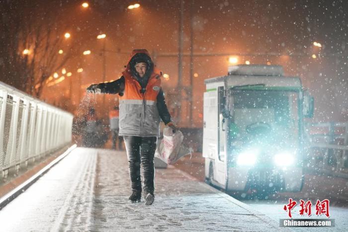 1月5日晚,北京迎来2020年首场降雪。图为环卫工人撒融雪剂,防止道路结冰。 中新社记者 张兴龙 摄 中新社记者 张兴龙 摄