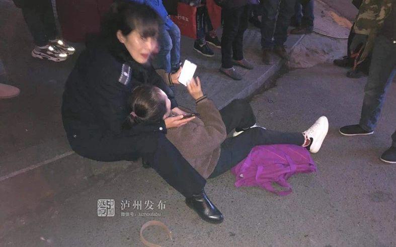 """老人街头摔倒,泸州一城管席地而坐当40分钟""""靠垫""""图片"""