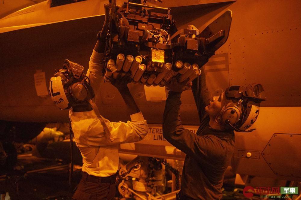 杜鲁门号航母的维护人员在夜间为战斗机安装弹射座椅系统
