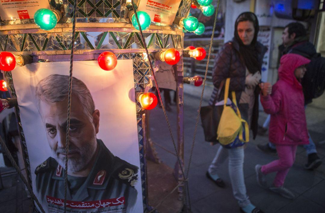 """▲1月5日,在伊朗首都德黑兰,人们走过悼念伊朗伊斯兰革命卫队下属""""圣城旅""""指挥官苏莱曼尼的海报。(新华社)"""