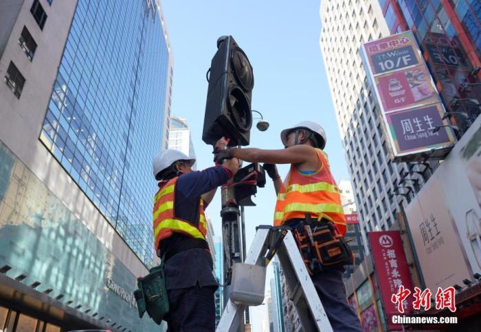 资料图:工程人员正在香港旺角弥敦道抢修早前被示威者破坏的交通信号灯。中新社记者 张炜 摄