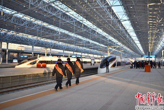 """12月30日,北京至张家口高速铁路开通运营,京张高铁设计时速350公里,全线设北京北、清河、沙河(不办理客运)、昌平、八达岭长城、东花园北、怀来、下花园北、宣化北、张家口10座车站。京张高铁是我国首条智能化高速铁路,也是2022年冬奥会的""""门户工程""""。北京北站站台,三名站务人员走向一辆即将发车的京张高铁列车。 实习生 宋欣然/摄"""