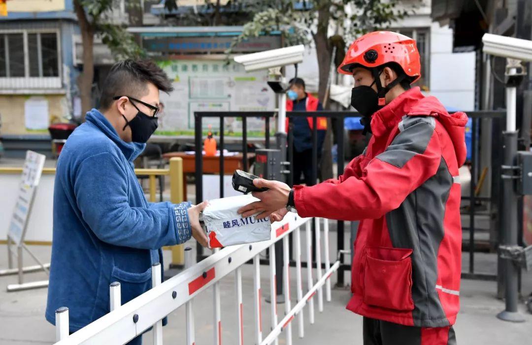 2月3日,西安一名快递员在一小区门口将货品交给收货人。新华社记者 刘潇 摄