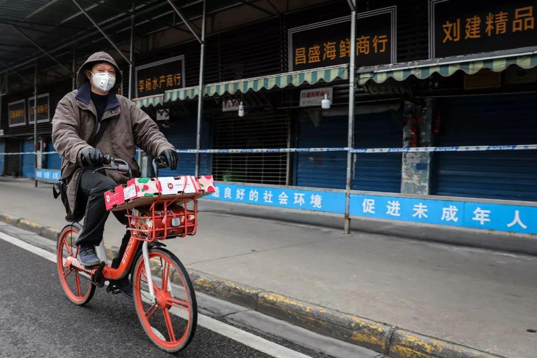 一位戴着口罩的市民骑车经过华南海鲜市场。