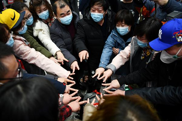 2月9日,在天津滨海国际机场,天津市第五批支援湖北医疗队启程。医疗队员和前来送行的人围成一圈加油打气。新华社 图