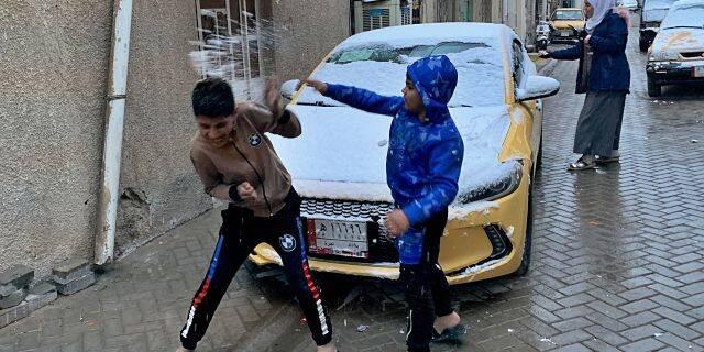 伊拉克儿童在巴格达的雪地里玩耍。(图源:美联社)