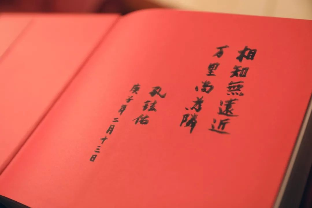 2月13日,中国驻日本大使孔铉佑向旗袍女孩赠送《中国世界遗产影像志》上的题字。新华社记者 杜潇逸 摄