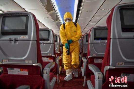 资料图:身着防护服的工作人员对航班客舱进行消毒作业。中新社记者 骆云飞 摄