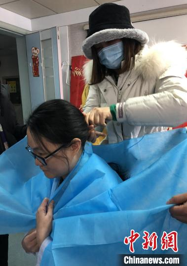 图为庞静在同事帮助下剪头发 钟欣 摄
