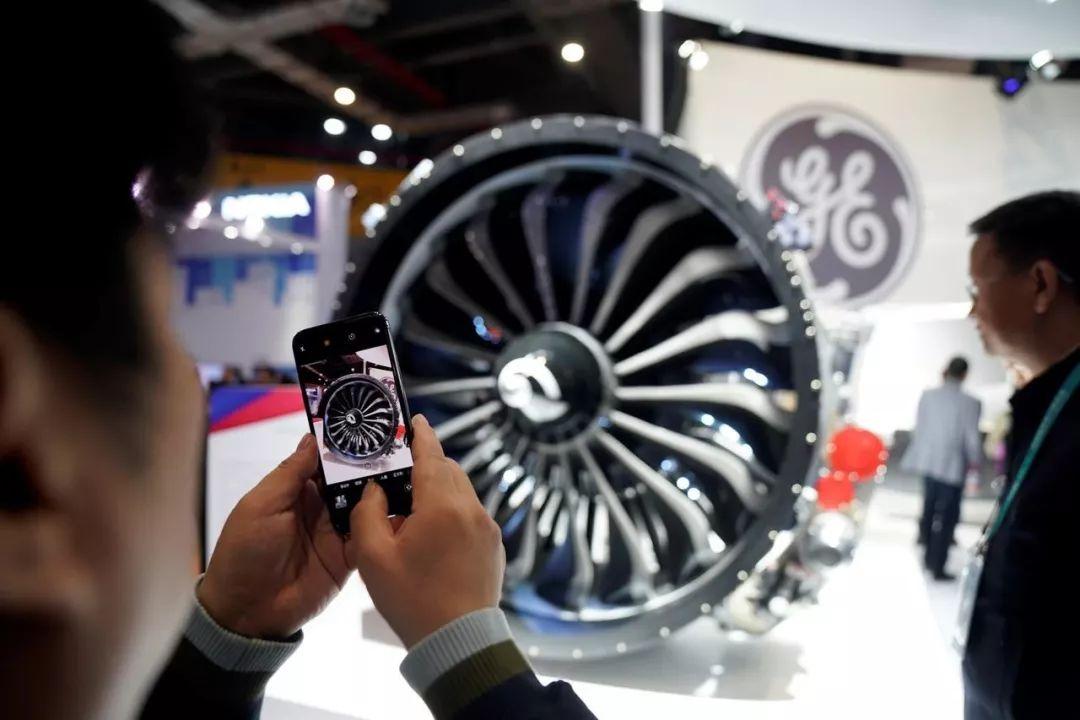 ▲资料图片:2018年11月,上海,一名男子在首届中国国际进口博览会上拍摄通用电气展示的发动机。(路透社)