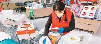 线上果蔬订单增多,京东七鲜超市的工作人员正加紧分装物品。   图片来源:京东