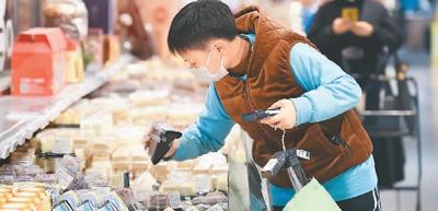 """卫引从北京青年公社餐厅青年路店加入盒马鲜生北京十里堡店,成为一名""""共享员工""""。图为卫引为外送订单拣货。   新华社记者 鞠焕宗摄"""