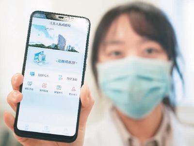 近日,江苏省人民医院互联网医院在原有基础上增设新冠肺炎的网络门诊,已接待1000余人次网上咨询。图为信息处的工作人员展示手机端的互联网医院平台。   新华社记者 季春鹏摄