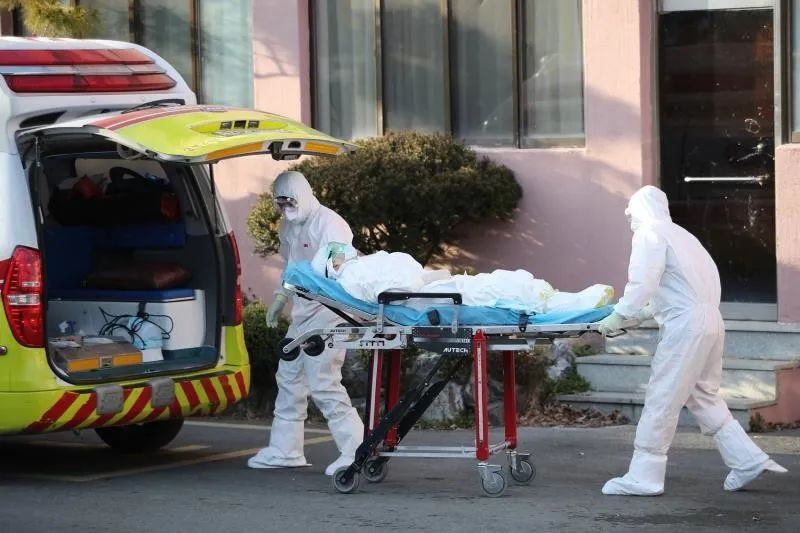 2020年2月21日,韩国大邱,身穿防护服的工作人员正在转运一名新冠肺炎疑似患者。图/法新